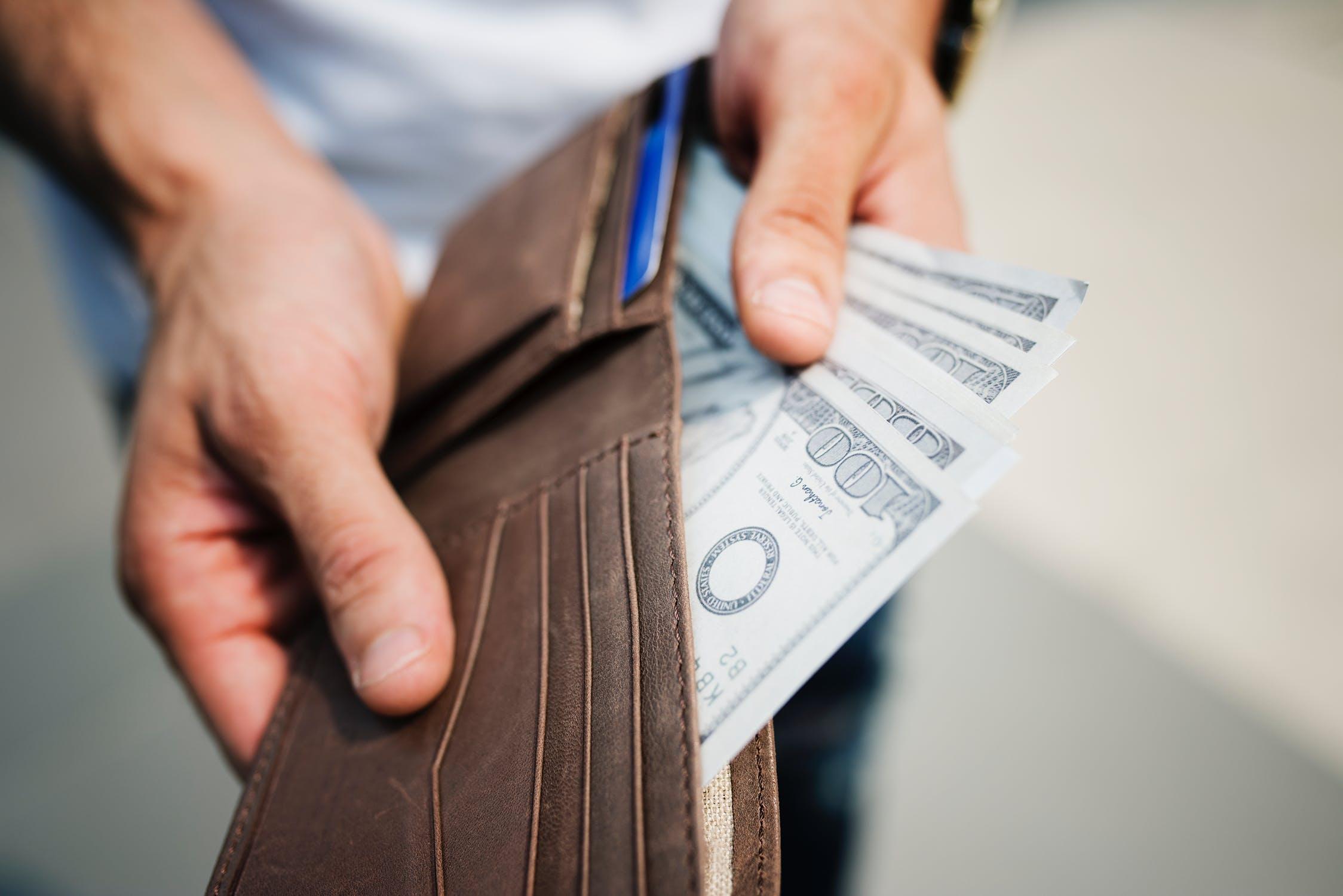 صورة Man Holding Brown Leather Bi-fold Wallet With Money in It